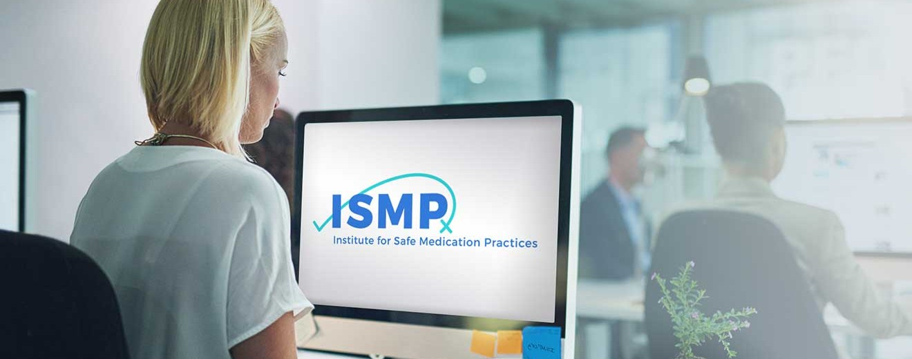 Woman sitting and looking at a computer screen with an ISMP logo
