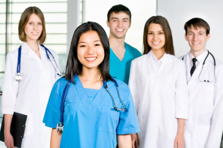 Healthcare practitioners standing in group, Three women, two men